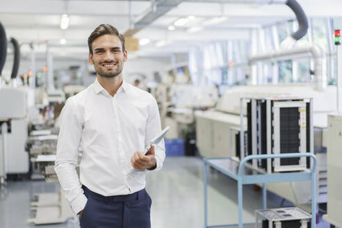 Smiling confident young businessman holding digital tablet while standing with hands in pockets at illuminated factory - MOEF03316