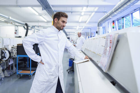 Young male technician in lab coat looking at reports on machinery - MOEF03334
