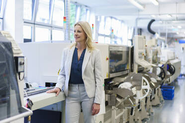 Thoughtful mature blond businesswoman standing by machinery while looking away at illuminated industry - MOEF03367