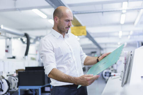 Confident mature male engineer analyzing large circuit board at illuminated factory - MOEF03376