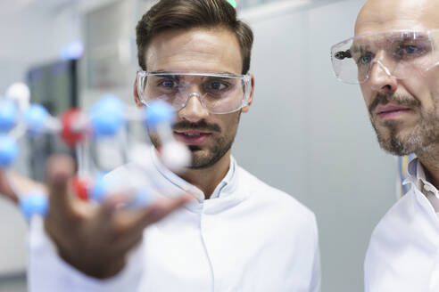 Confident male scientists analyzing molecular structure at illuminated laboratory - MOEF03394