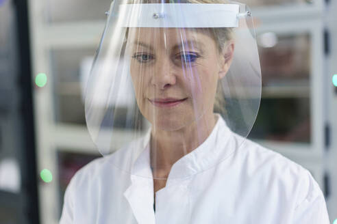 Close-up of mature female scientist wearing protective face shield at laboratory - MOEF03400