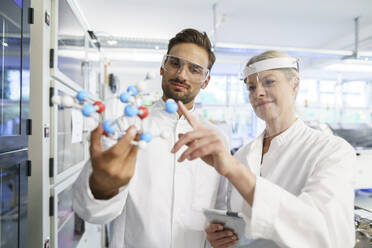 Smiling female scientist touching molecular structure held by young male colleague at laboratory - MOEF03406