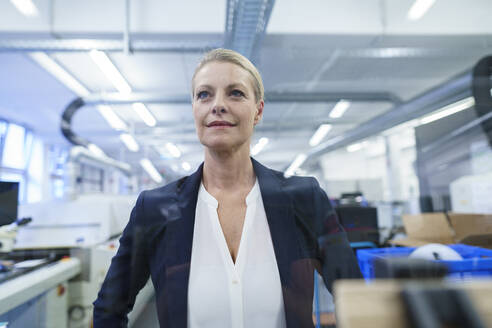 Confident blond businesswoman standing while looking away in illuminated factory - MOEF03412