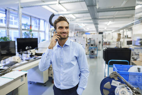 Smiling young male professional talking on smart phone while standing at illuminated factory - MOEF03418