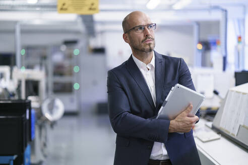 Businessman holding digital tablet while looking away at bright factory - MOEF03442