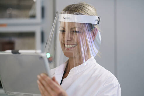 Happy mature female scientist wearing protective face shield while using digital tablet at laboratory - MOEF03460