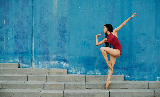 Side view of flexible ballerina in pointe shoes and bodysuit dancing on street near blue building while balancing on leg - ADSF15708