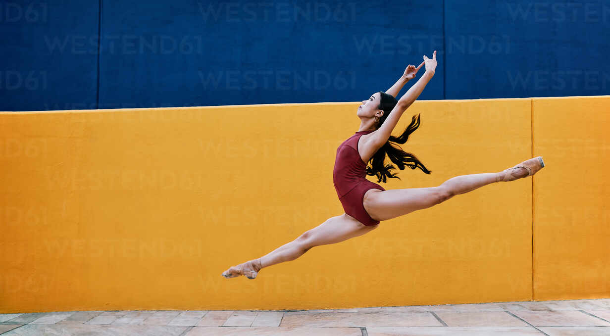 Side view of flexible ballerina wearing pointe shoes and bodysuit in moment of jumping with raised arms in city - ADSF15711 - ADDICTIVE STOCK CREATIVES/Westend61