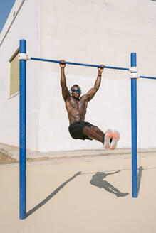 Full length of shirtless athletic African American male doing exercise on fitness equipment while training alone on sports ground - ADSF15819