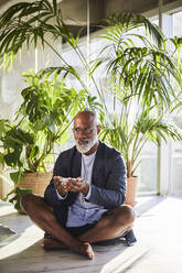 Mature man holding bowl while sitting at home - FMKF06365