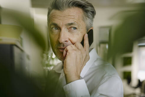 Man talking on phone while standing at office - JOSEF01956