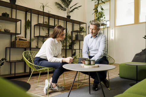 Businessman and woman discussing while working on digital tablet at office - JOSEF02034