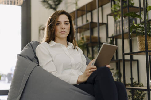 Businesswoman using digital tablet while sitting on beanbag at office - JOSEF02037