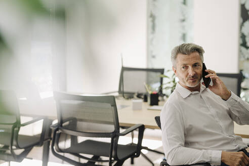 Businessman talking on phone while sitting on chair at office - JOSEF02058