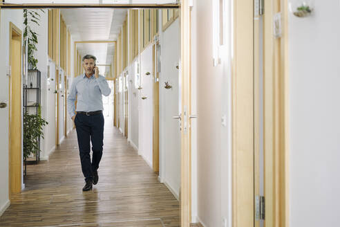 Businessman talking on mobile phone while walking at corridor in office - JOSEF02082