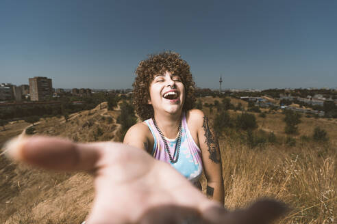 Smiling woman showing hand while standing against clear sky - DAMF00501