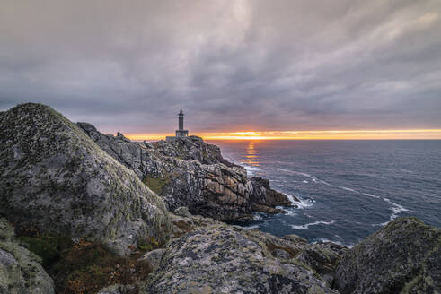 Spectacular scenery of lighthouse located on rough cliff near sea on background of sundown sky - ADSF15834