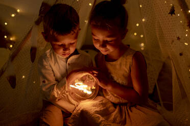 Sibling holding light while sitting in room during christmas - GMLF00649