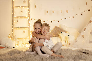 Brother and sister embracing each other in room - GMLF00658