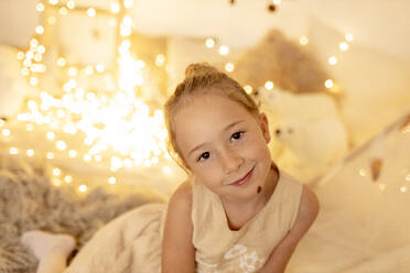 Little girl smiling while sitting in room during christmas - GMLF00661