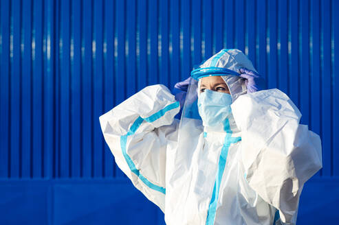 Nurse wearing face shield while standing against blue wall on sunny day - PGF00119