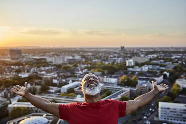 Happy bearded man with arms outstretched while standing on building terrace in city during sunset - FMKF06418
