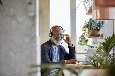Smiling businessman listening through headphones while sitting with laptop at table and working from home - FMKF06433