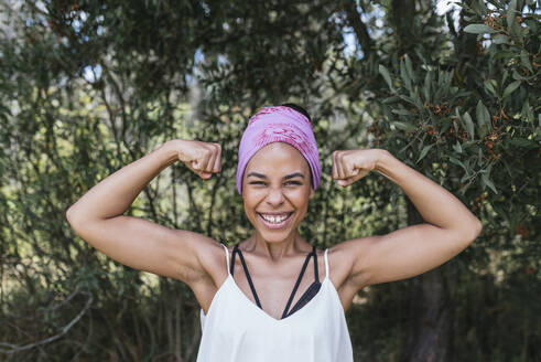 Happy woman with purple bandana flexing muscles while standing against plants at park - DSIF00147