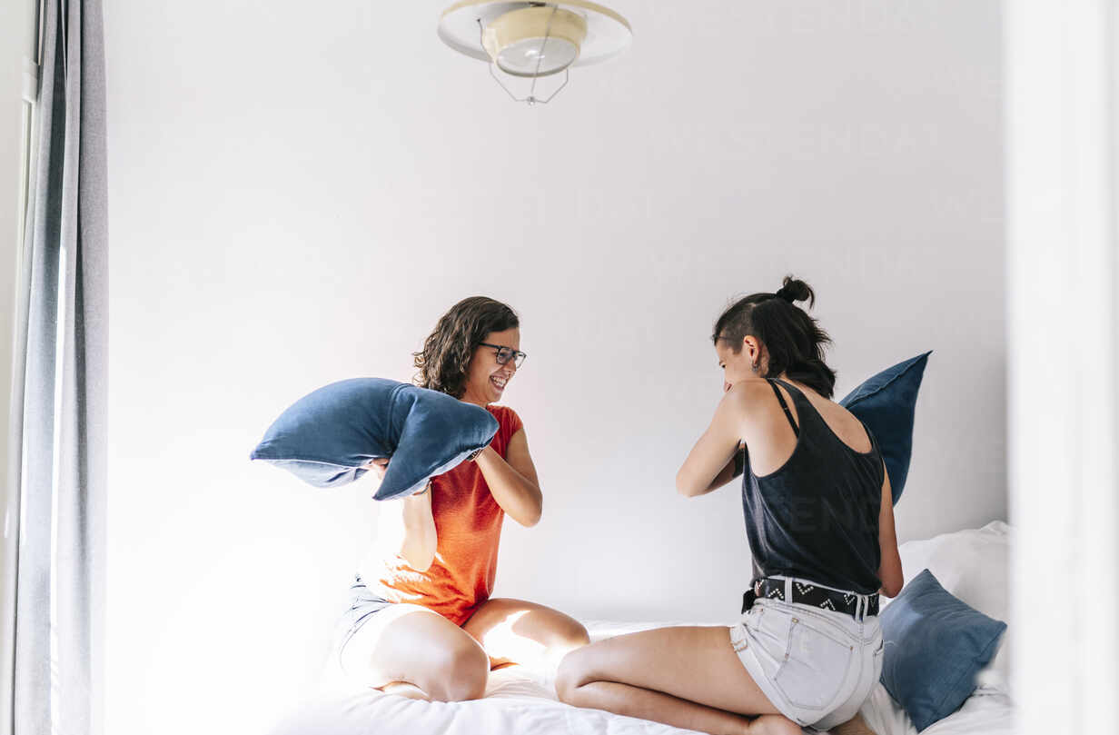 Friends Enjoying Pillow Fight In Bedroom At Home Stockphoto