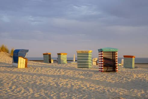 Striped tents at beach against cloudy sky during sunset - WIF04337