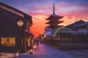 Ancient temple by traditional street against cloudy sky during sunset, Kyoto - LCUF00114