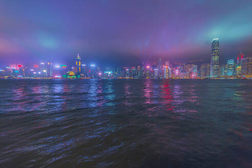 Illuminated buildings in city in front of sea against sky at night, Hong Kong - LCUF00117