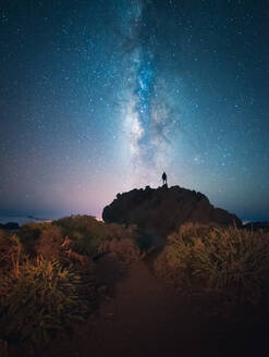 Back view of unrecognizable traveler male standing on hill while admiring spectacular scenery of milky way over mountainous in starry night - ADSF15924