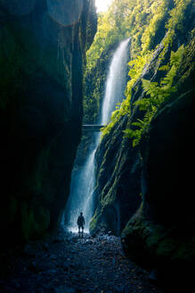 Back view of unrecognizable person walking of spectacular scenery of waterfall in long exposure in woods with green plants in highland area - ADSF15939