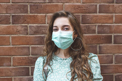 Woman wearing face mask against brick wall during COVID-19 outbreak - EYAF01342