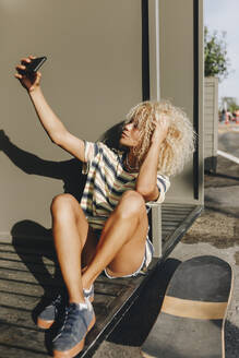 Blond woman taking selfie through smart phone while sitting against metallic wall - MRRF00526