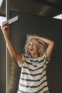 Woman taking selfie through smart phone while making faces against metallic wall - MRRF00529