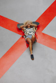 Blond Afro woman lying with head in hands on orange road marking - MRRF00541