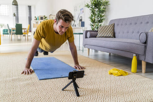 Young man looking at mobile phone while exercising on mat at home - GIOF08931