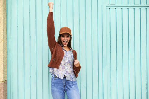 Young woman with hand raised screaming while standing against blue metal door - KIJF03294