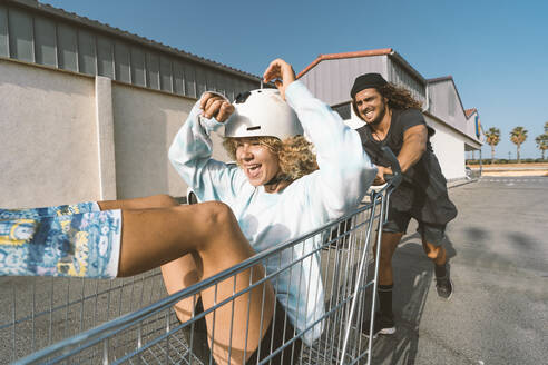 Playful young man pushing girlfriend sitting in shopping cart outside supermarket on sunny day - DAMF00507