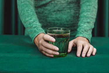 Midsection of woman holding glass of cocktail drink kept on table - ERRF04513