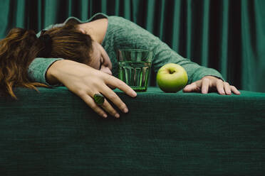 Woman lying on table with cocktail drink and green apple - ERRF04519