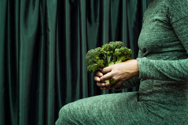 Midsection of woman holding broccoli while sitting by green curtain - ERRF04522