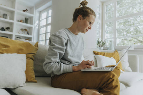 Mid adult woman working on laptop while sitting on sofa at home - MFF06198