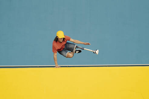 Disabled athlete doing handstand against multi colored wall - JCZF00274