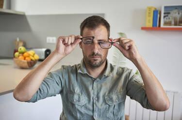 Mid adult man holding broken eyeglasses while sitting at home - VEGF02983