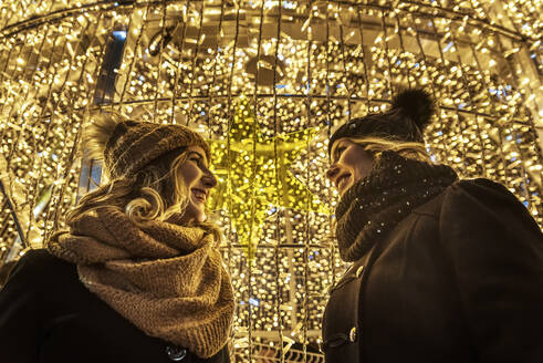 Two young girls are laughing in the background of Christmas lights - CAVF89761