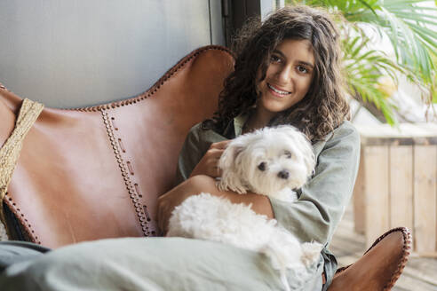 Smiling girl holding puppy while sitting on chair at home - DLTSF01308